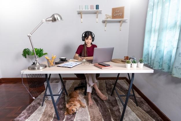 彼女のペットと一緒に家で働く若い美しいアジアの女性