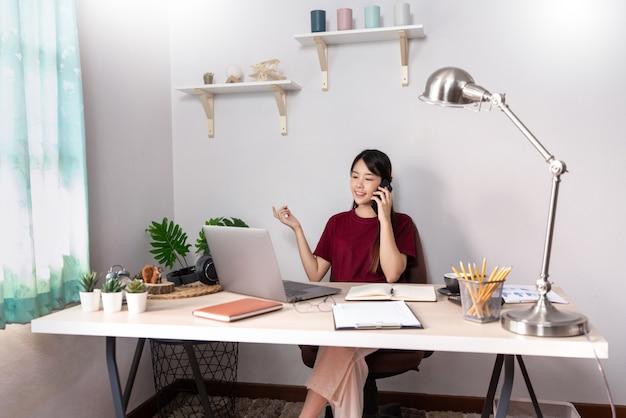 Молодая красивая азиатская женщина работая дома