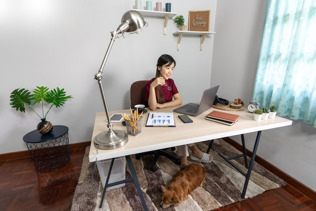 Young beautiful asian woman working at home with her dog