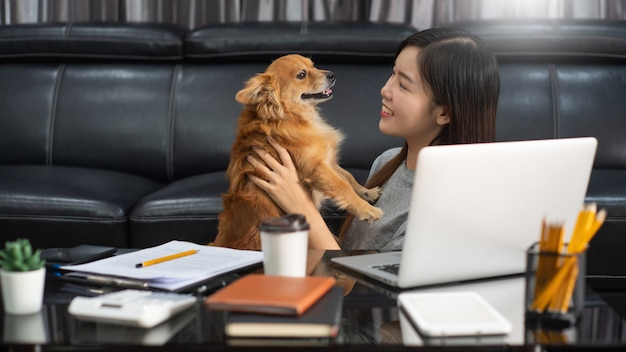 Young beautiful asian woman working at home with her pet