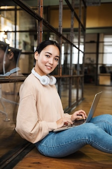Young beautiful asian woman working on laptop while sitting on floor in office