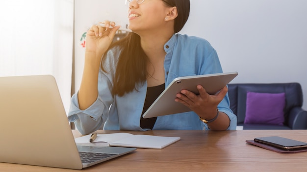 Young beautiful asian woman working with laptop,smartphone and tablet in home office background