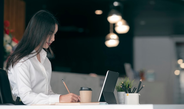 Young beautiful asian woman writing somethings with pencil while sitting at her office desk in modern office room.