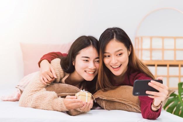 若い美しいアジア女性のレズビアンカップルの恋人は、ギフトボックスと自宅のベッドルームでスマートフォンでselfieを与えると笑みを浮かべて。幸せなライフスタイルとlgbtセクシュアリティの概念。