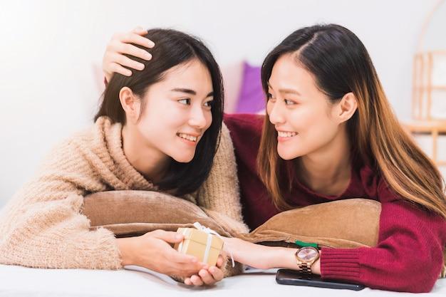 若い美しいアジア女性のレズビアンカップルの恋人は、笑顔で自宅のベッドルームでギフトボックスを与えます。一緒に幸せなライフスタイルとlgbtのセクシュアリティの概念。
