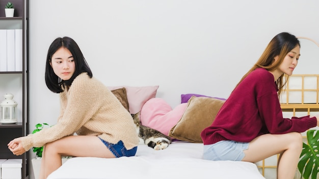 Young beautiful asian women lesbian couple lover having stressed after conflict each other in bed room at home with moody emotion. concept of lgbt sexuality with upset and unhappy lifestyle together.