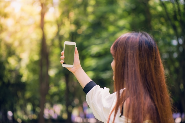 Young beautiful asian women with long brown hair taking a selfie on her phone in the park. natural lighting, vibrant colors.