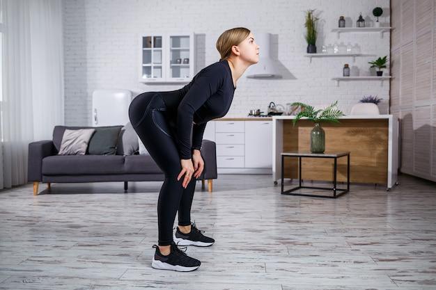 Молодая красивая спортивная девушка в леггинсах и топе делает упражнения на растяжку. здоровый образ жизни. женщина занимается спортом дома.