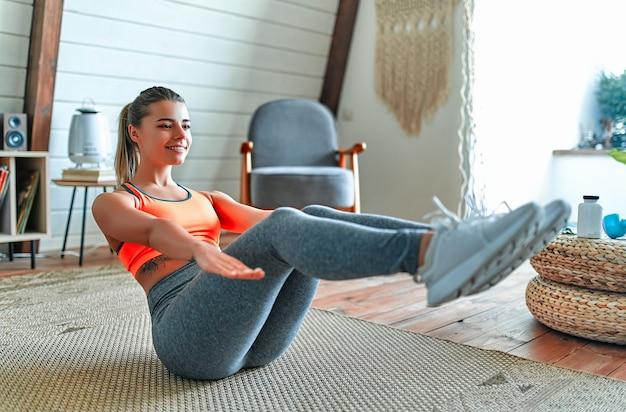 레깅스와 상의를 입은 젊고 아름다운 운동 소녀는 복부 운동을 합니다. 건강한 생활. 여자는 집에서 운동을 하러 간다.
