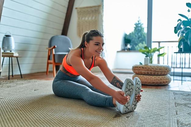 레깅스와 상의를 입은 젊고 아름다운 운동 소녀는 스트레칭 운동을 합니다. 건강한 생활. 여자는 집에서 운동을 하러 간다.