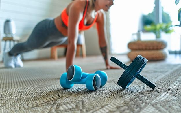 レギンスとトップの若い美しい運動少女は、運動板を作ります。健康的な生活様式。女性は家でスポーツに行きます。手前にはダンベルがあります。