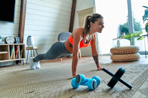 レギンスとトップの若い美しい運動少女は、運動板を作ります。健康的な生活様式。女性は家でスポーツに行きます。
