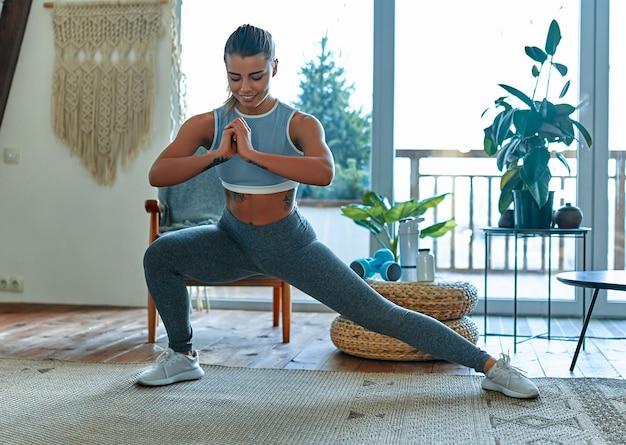 Молодая красивая спортивная девушка в леггинсах и топе делает выпады. здоровый образ жизни. женщина делает упражнения дома.