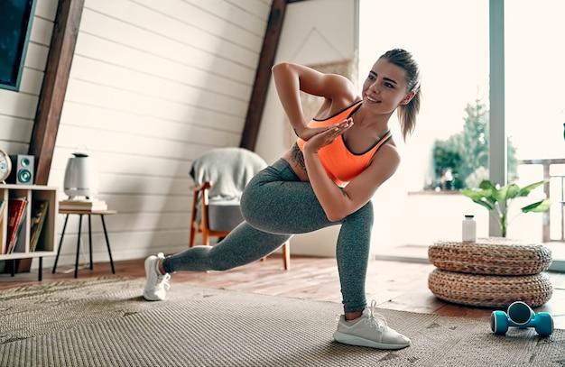 레깅스와 상의를 입은 젊고 아름다운 운동 소녀가 돌진을 만듭니다. 건강한 생활. 집에서 운동을 하는 여자.