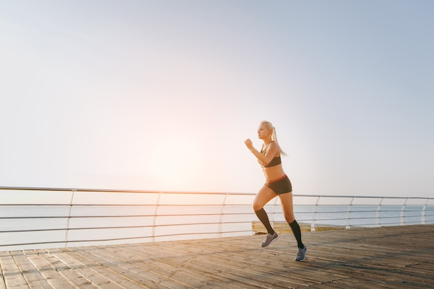 The young beautiful athletic girl with long blond hair in black clothes running at sunrise over the sea