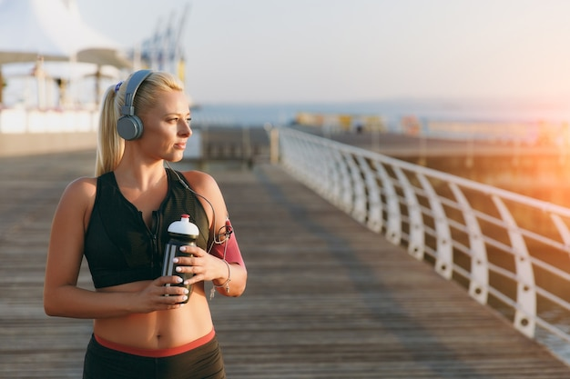 The young beautiful athletic girl with long blond hair in headphones and a bottle of water in hands looking at the sea at dawn