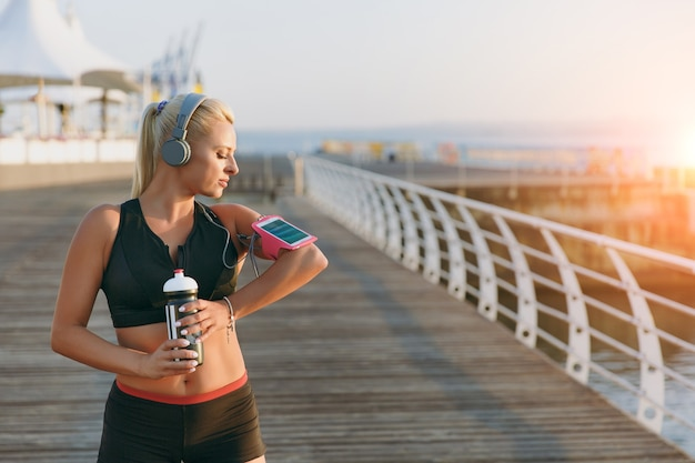 The young beautiful athletic girl with long blond hair in headphones and a bottle of water in hands looks at mobile phone on hand by the sea at dawn
