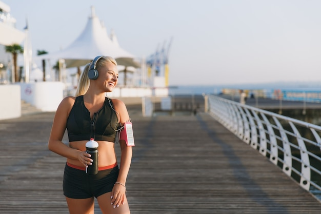 The young beautiful athletic girl with long blond hair in headphones and a bottle of water in hands looks at the sea at dawn