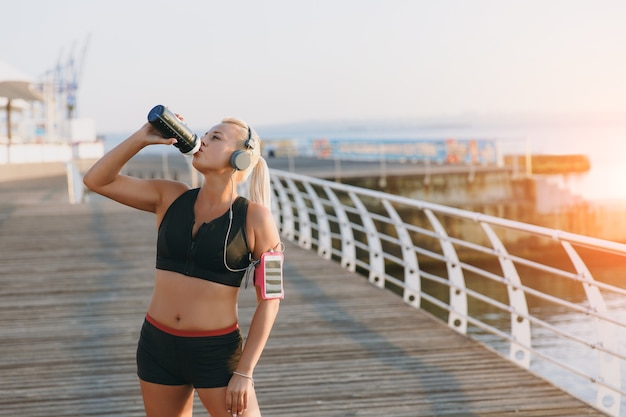 The young beautiful athletic girl with long blond hair in headphones drinks water from a bottle at dawn by the sea