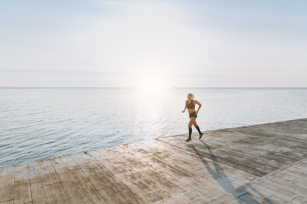 The young beautiful athletic girl with long blond hair in headphones listening to music and running at sunrise over the sea