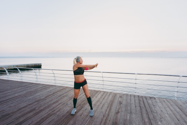 The young beautiful athletic girl with long blond hair in headphones listening to music and training at sunrise over the sea
