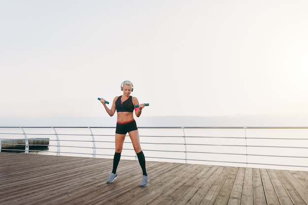 The young beautiful athletic girl with long blond hair in headphones, listening to music and training with dumbbells at sunrise over the sea