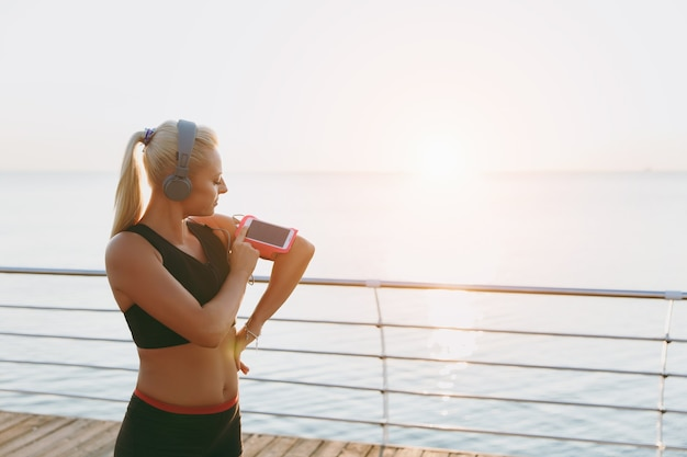 The young beautiful athletic girl with long blond hair in headphones looks at mobile phone at sunrise over sea