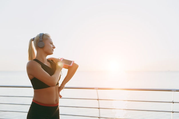 The young beautiful athletic girl with long blond hair in headphones looks at the sea at dawn