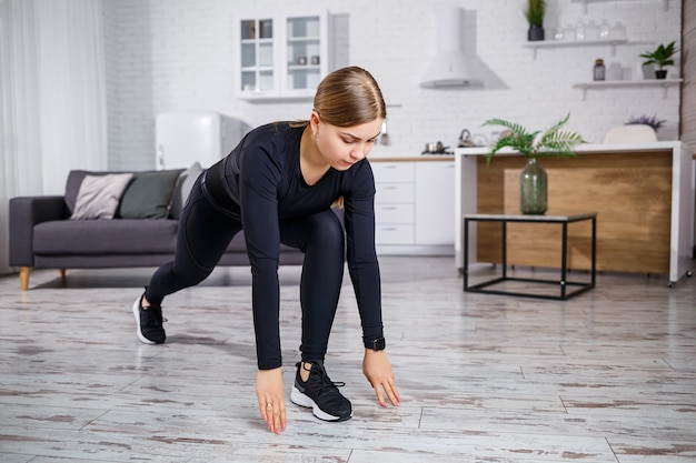 Young beautiful athletic woman in black leggings and top doing warm-up exercises at home. healthy lifestyle. girl in fitness clothes. the woman goes in for sports at home.