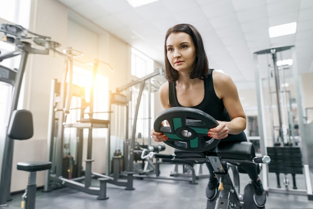 Young beautiful athletic woman brunette doing fitness exercises in the gym.