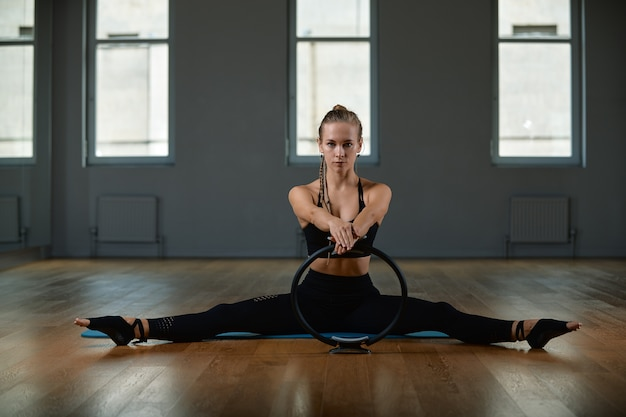 A young, beautiful, athletic woman does exercises with a pilates ring in the gym. sports slavic woman in a black suit.