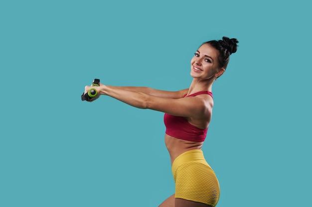 그녀의 앞에 뻗은 아령과 포즈와 파란색 배경에 서있는 동안 카메라에 행복 하 게 웃 고 젊은 아름 다운 운동 여자.
