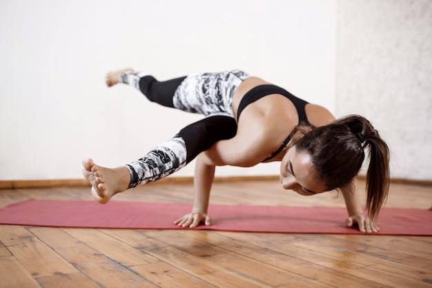 Young beautiful athletic woman practicing indoor yoga arm-balance eka pada koundiyanasana