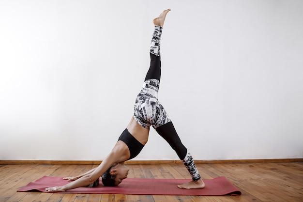 Giovane bella donna atletica che si esercita in yoga dell'interno sulla stuoia rossa