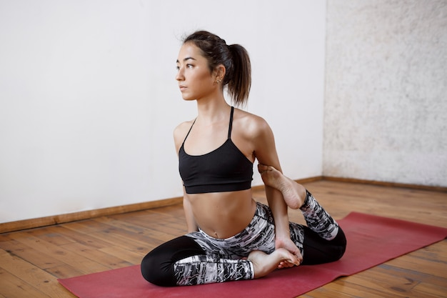 Young beautiful athletic woman practicing indoor yoga on red mat