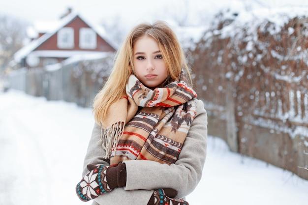 休暇中にスタイリッシュな暖かいスカーフでウールのミトンのヴィンテージグレーのコートを着た若い美しい魅力的な田舎の女性は、冬の日に田舎を歩きます。かわいい女の子。