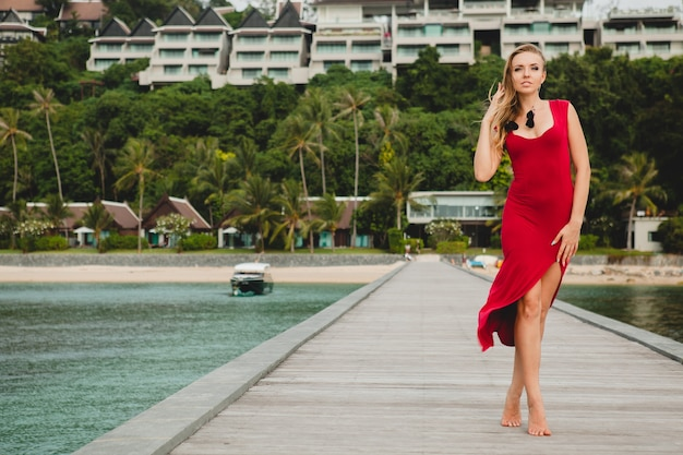 Молодая красивая привлекательная женщина, стоящая одна на пирсе в роскошном курортном отеле, летние каникулы, красное длинное платье, светлые волосы, сексуальная одежда, тропический пляж, соблазнительная, чувственная, улыбающаяся