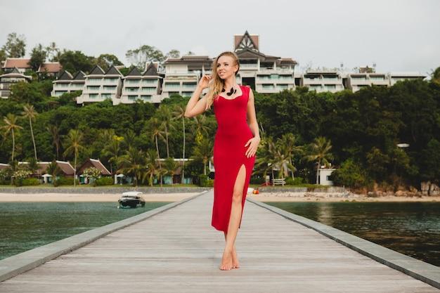 高級リゾートホテルの桟橋に一人で立っている若い美しい魅力的な女性、夏休み、赤いロングドレス、ブロンドの髪、セクシーなアパレル、熱帯のビーチ、魅惑的な、官能的な、笑顔