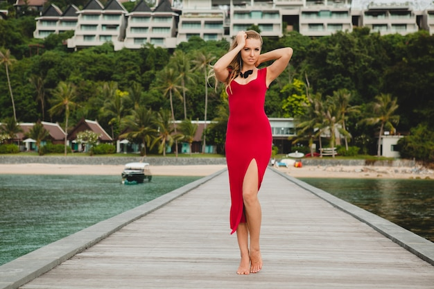 Young beautiful attractive woman standing alone on pier in luxury resort hotel, summer vacation, red long dress, blond hair, sexy apparel, tropical beach, seductive, sensual, smiling