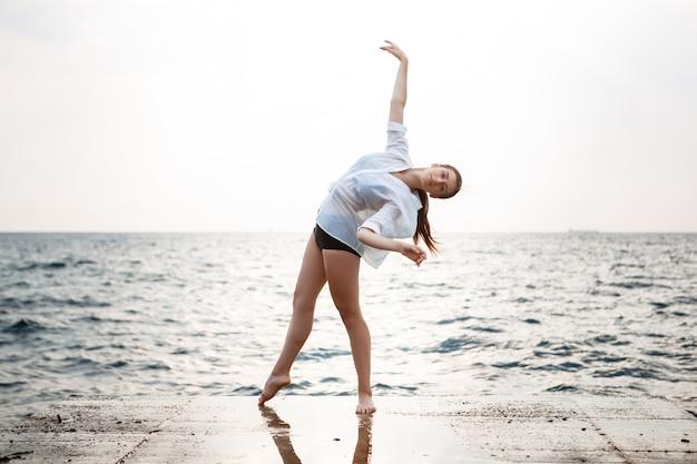 Giovane bella ballerina che balla e che posa fuori, diga