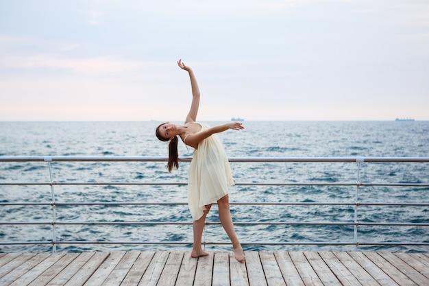 Giovane bella ballerina che balla e che posa fuori