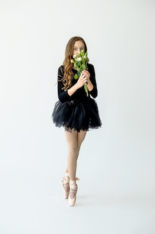 A young beautiful ballerina girl stands on pointe shoes in a black swimsuit and skirt with flowers in her hands on a light background.