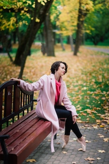 フェアコートとトウシューズを履いた若い美しいバレリーナがベンチに座り、秋の公園で屋外で休憩します。