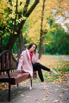 공정한 코트와 pointe 신발에 젊은 아름다운 발레리나는 벤치에 앉아 가을 공원에서 야외에서 휴식을 취합니다.