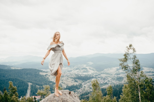 Young beautiful barefoot blonde girl with long hair in summer dress standing on top of mountain