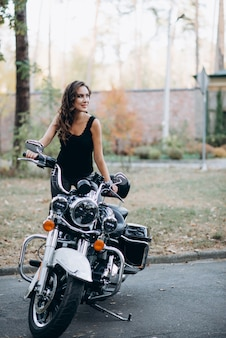 Young beautiful biker girl in a black tank top and leather pants on a motorcycle. the concept of speed and freedom