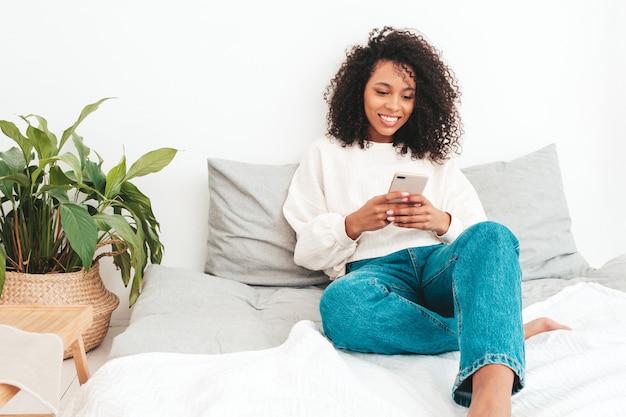 アフロカールの髪型を持つ若い美しい黒人女性。笑顔のモデルは、朝の白いインテリアの寝室のベッドに横たわっています