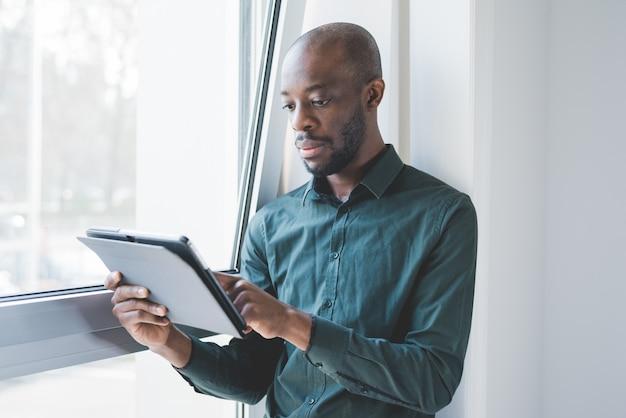 Young beautiful black man indoor using tablet