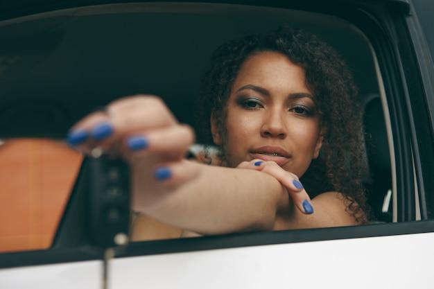 그녀의 새 차를 운전하는 차 열쇠를 들고 젊은 아름 다운 흑인 여성 드라이버