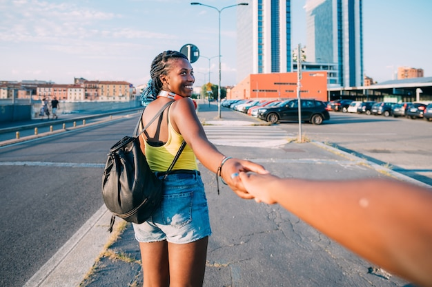Young beautiful black woman outdoor holding hand walking on the road, smiling